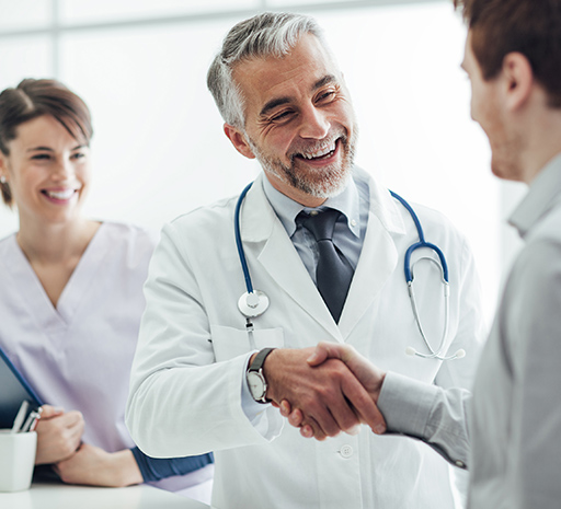 Smiling provider shaking hands with patient