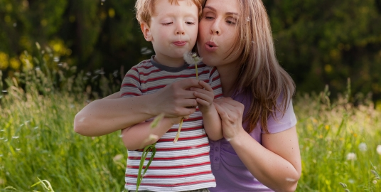 Mother and son blowing a dandelion